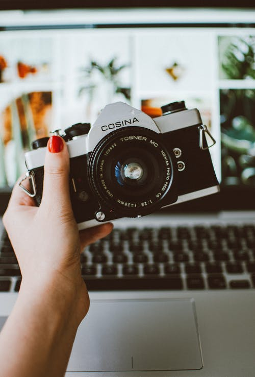 Woman Holding a Cosina Camera