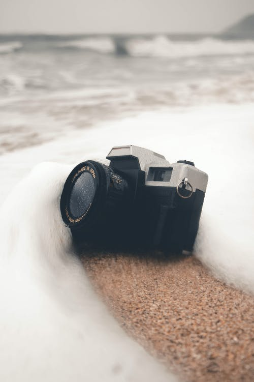 Black Camera on Brown Sand