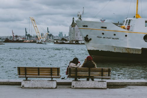 Women Sitting on the Bench Watching Sailing Ship