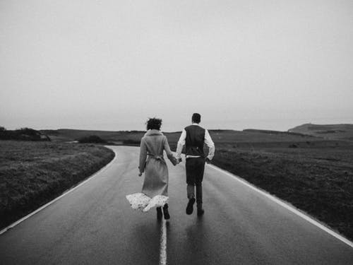 Grayscale Photo of Couple Walking on Road