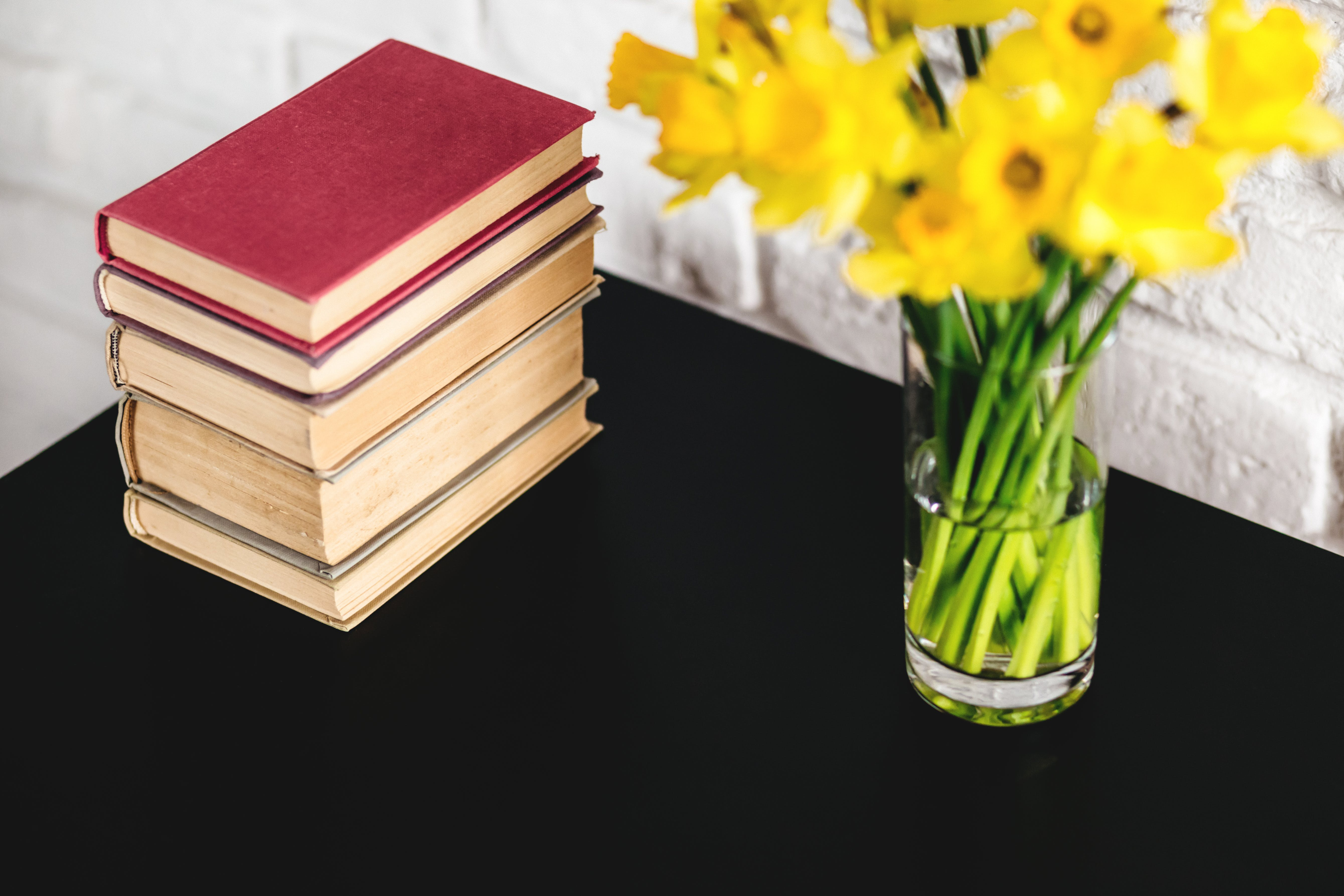 Hardbound Books Beside Yellow Petaled Flowers