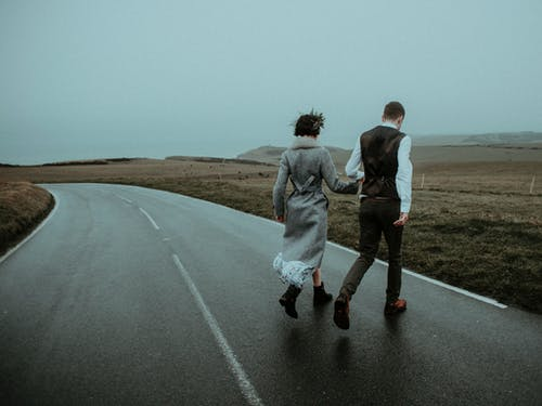Photo Of Couple Walking On Road