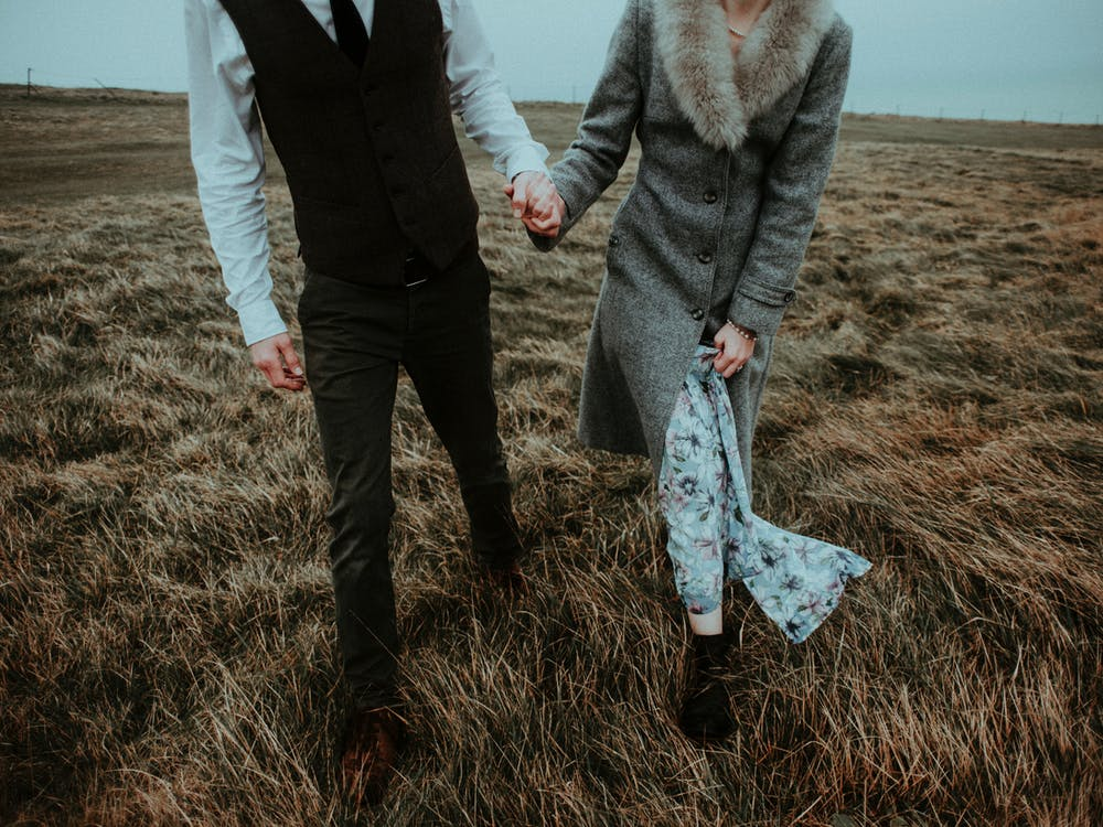 People holding hands while walking in a field. | Photo: Pexels