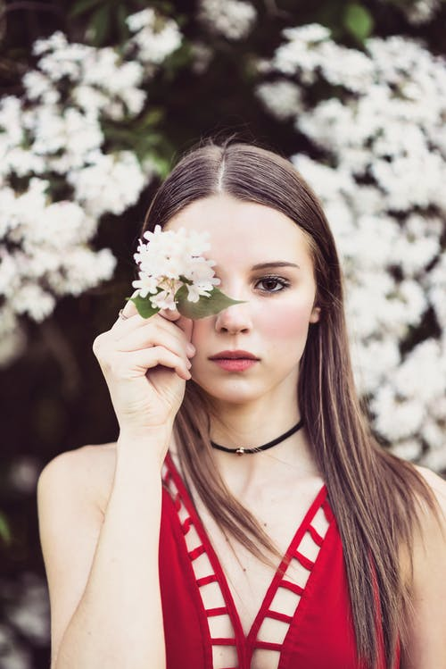 Woman in Red Tank Top Holding White Flowers