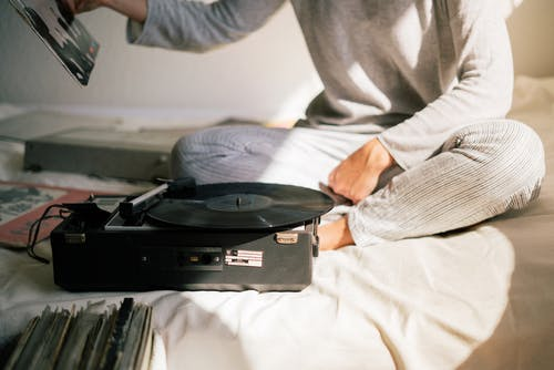 Person in Gray Sweater Holding Black Vinyl Record Player