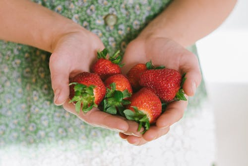 Person Holding Strawberries on Her Hands