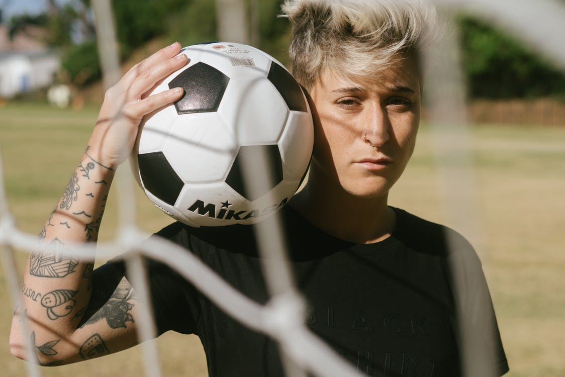 Person in Black Shirt Holding White and Black Soccer Ball