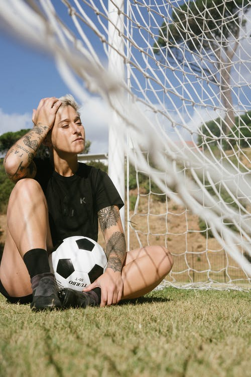Person in Black Crew Neck T-shirt Holding on White Soccer Ball