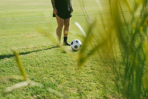 Woman in Black Shorts and Black Socks Standing on Green Grass Field