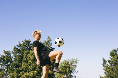 Person in Black Shirt and Black Shorts Holding Soccer Ball