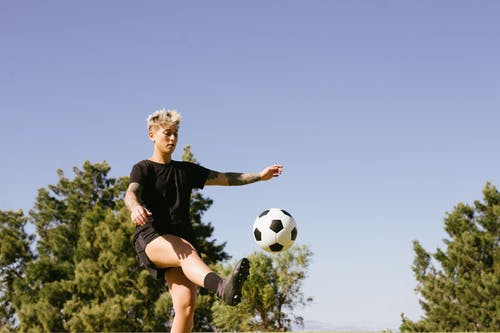 Woman in Black Shirt and Black Shorts Kicking Soccer Ball
