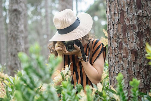 Woman in White Hat and Black and Yellow Stripe Tank Top Standing Beside Brown Tree during Day