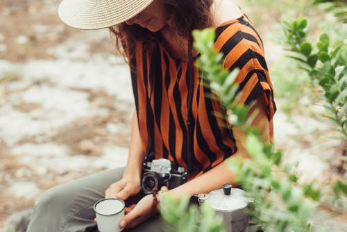 Woman in Orange and Black Stripe Shirt Holding Black and Silver Dslr Camera