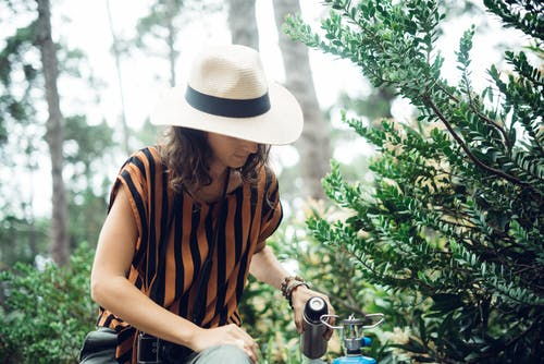 Woman in Brown and Black Stripe Shirt and Brown Hat Holding Cannester