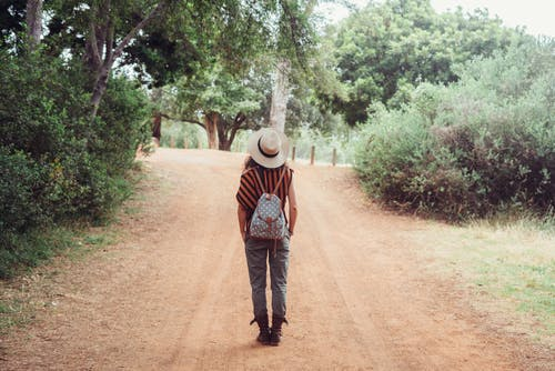 Woman Wearing a Hat Walking on Dirt Road