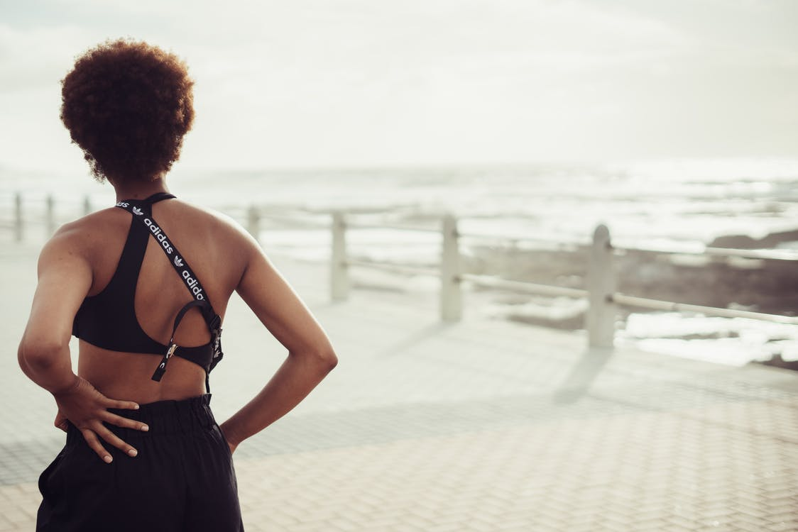 Selective Focus Back View Photo of Woman in Black Spaghetti Strap Top and Short Standing with Her Hands Akimbo