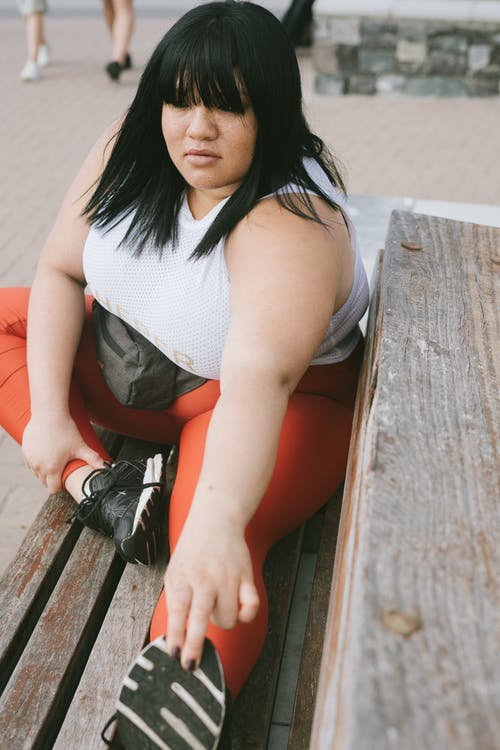 Woman In White Tank Top And Red Leggings Sitting On Brown Wooden Bench