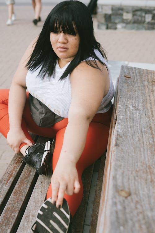 Mujer En Camiseta Blanca Sin Mangas Y Polainas Rojas Sentado En Un Banco De Madera Marrón