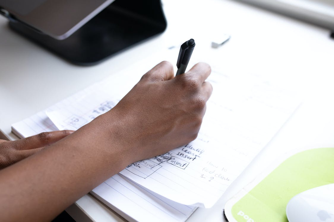 Crop faceless employee writing on paper during workday