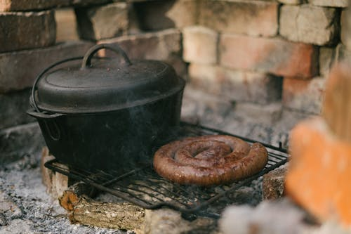 Footlong Sausage And Black Cooking Pot on Black Metal Grill