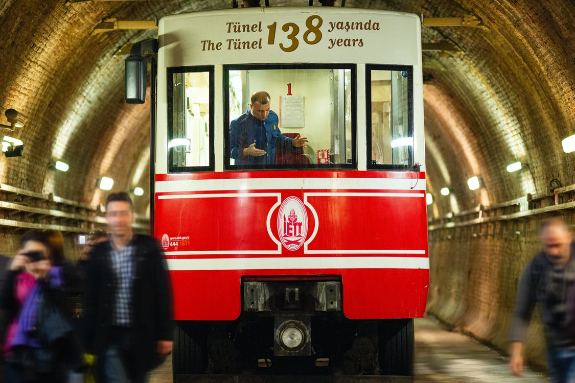 People Standing Beside Red and White Train