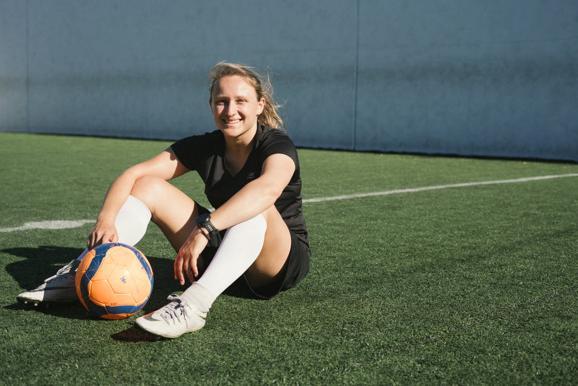 Soccer Player Sitting On A Green Field
