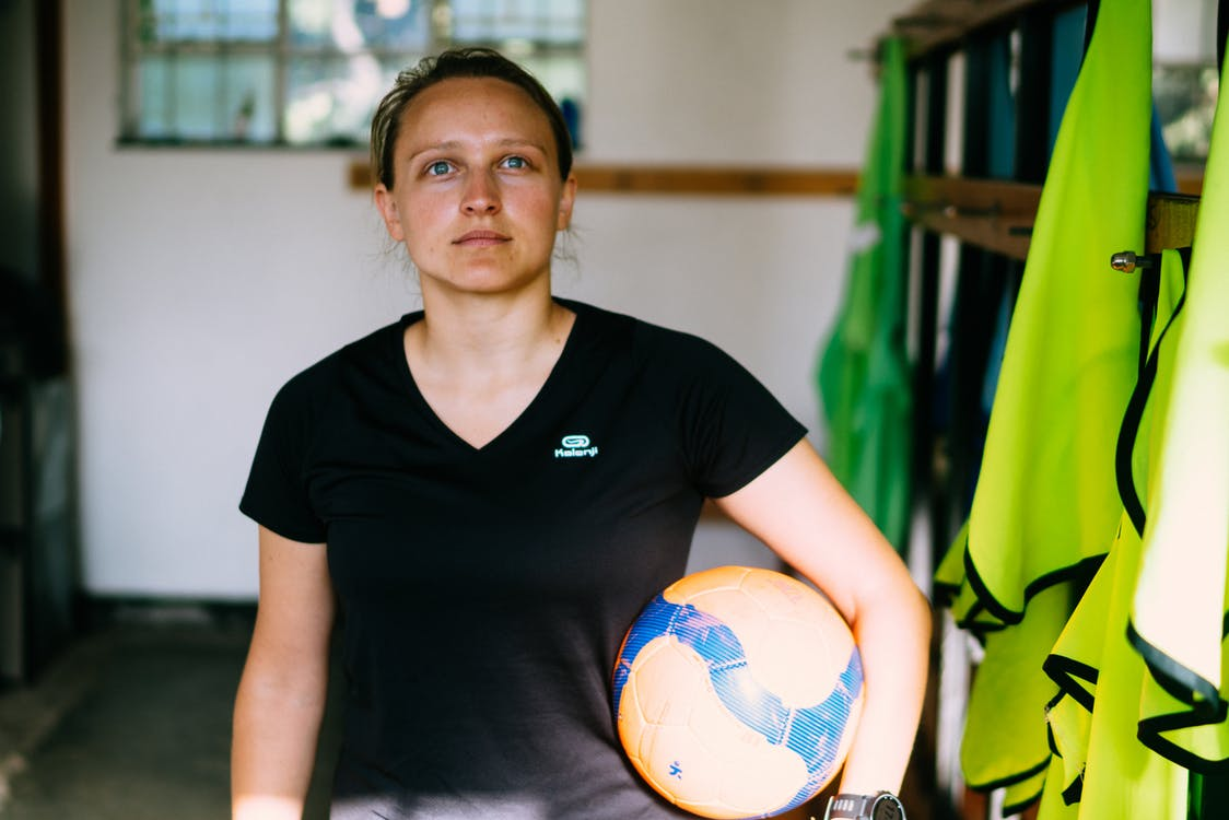 Woman in Black V Neck T-shirt Holding Yellow and Blue Soccer Ball