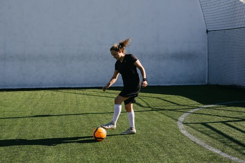 Woman in Black Shirt Playing Soccer