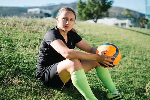 Woman in Black T-shirt and Green Socks Sitting on Green Grass Field