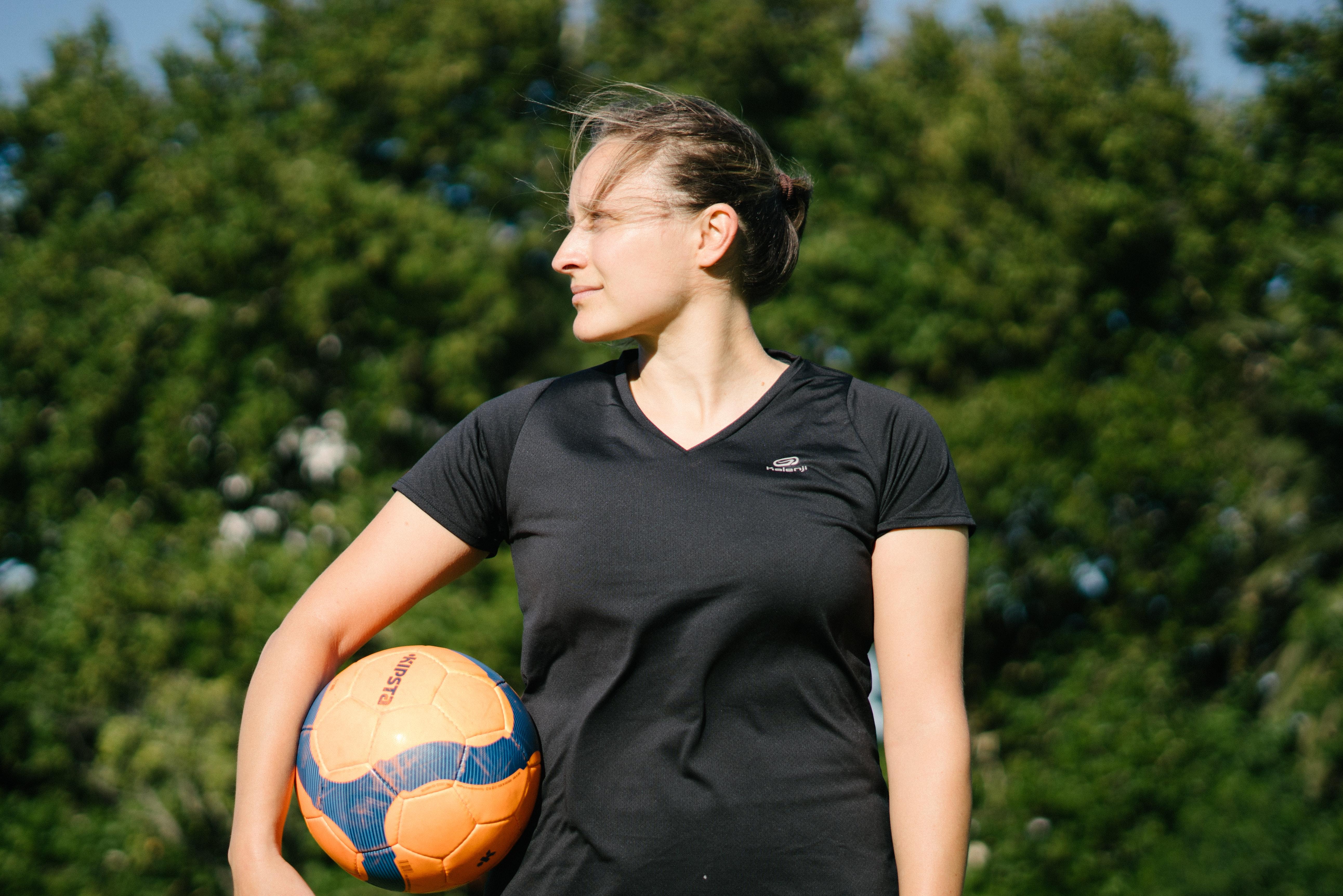 Mulher De Camiseta Preta Com Gola Redonda Segurando Uma Bola De Futebol · Foto profissional gratuita