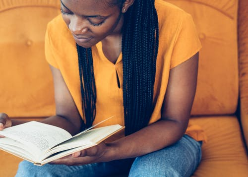 Woman In Yellow Shirt And Blue Denim Jeans Reading A Book