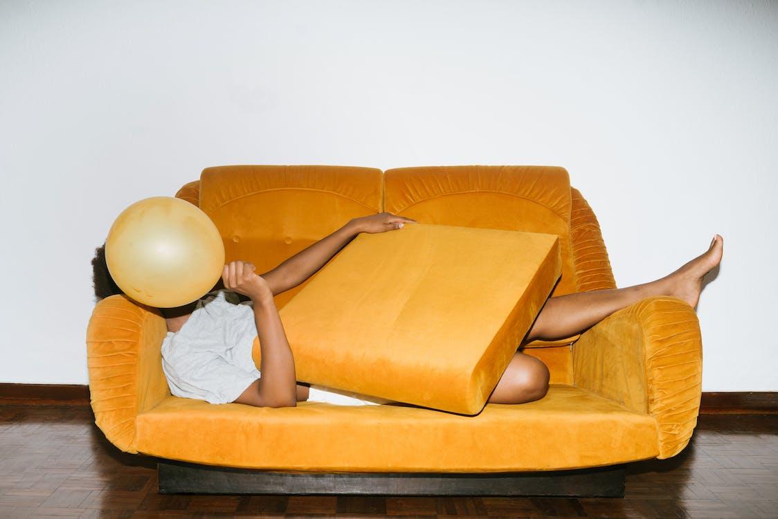 Person Lying On Orange Sofa