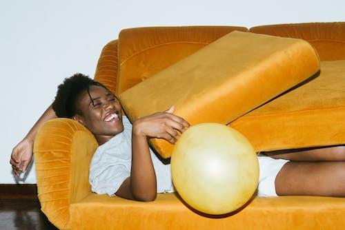 Person Lying On Yellow Sofa