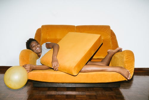 Woman Lying on Orange Sofa