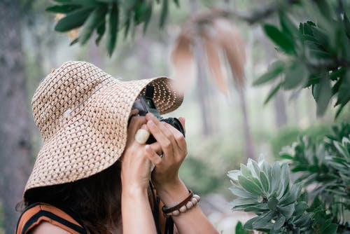 Woman In Brown Sun Hat Taking Photos