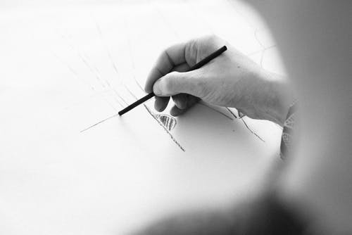 Person Sketching on White Surface