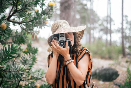 Woman Wearing Brown Sun Hat Holding A Camera