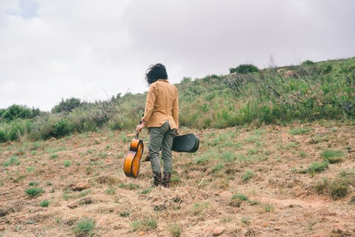 Person Standing on Grass Holding a Guitar