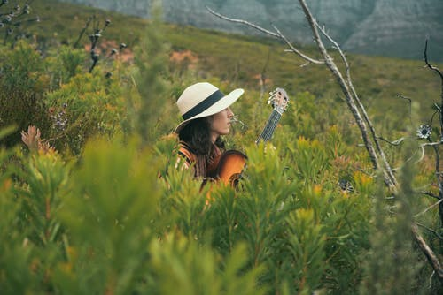 Woman Wearing Hat Playing a Guitar on Green Field