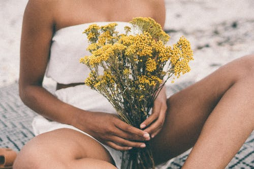 Woman in White shorts Holding Yellow Flower Bouquet
