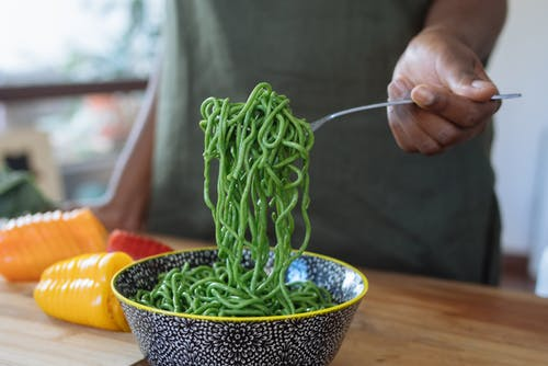 Person Holding Stainless Steel Fork With Green Noodles in  Blue Ceramic Bowl