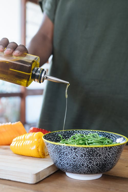 Person Pouring  Liquid on Green Noodles in Ceramic Bowl