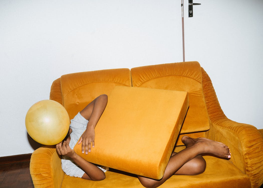 Person Lying On Brown Sofa Chair