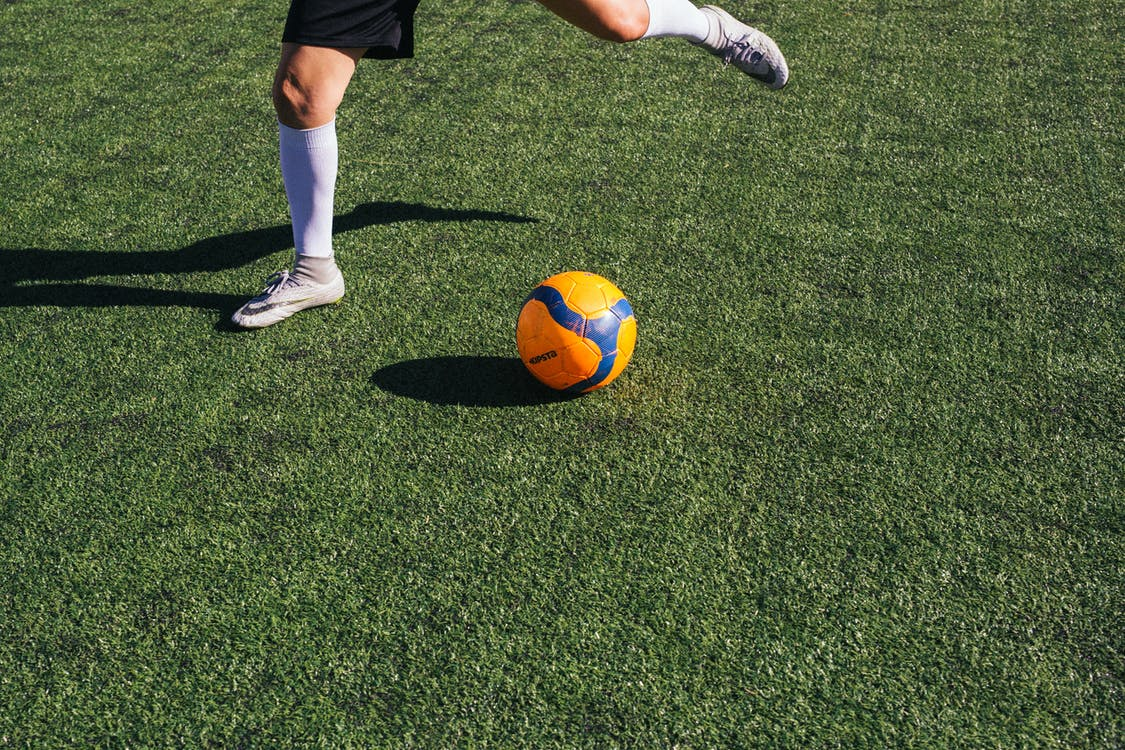 Person in Black Shorts and White Nike Sneakers Playing Soccer on Green Grass Field