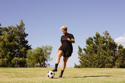 Person Wearing Black Shirt and Shorts Playing Soccer
