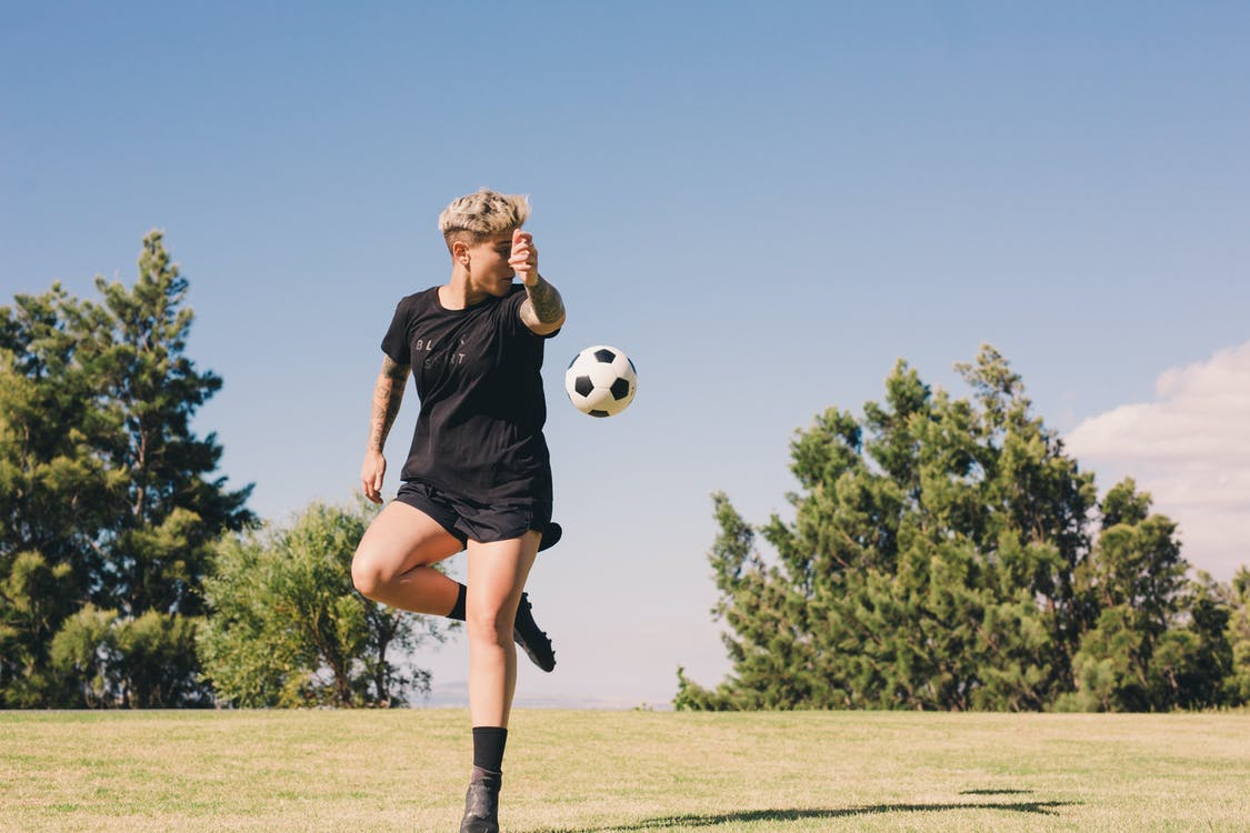 Woman Playing A Soccer In Green Field