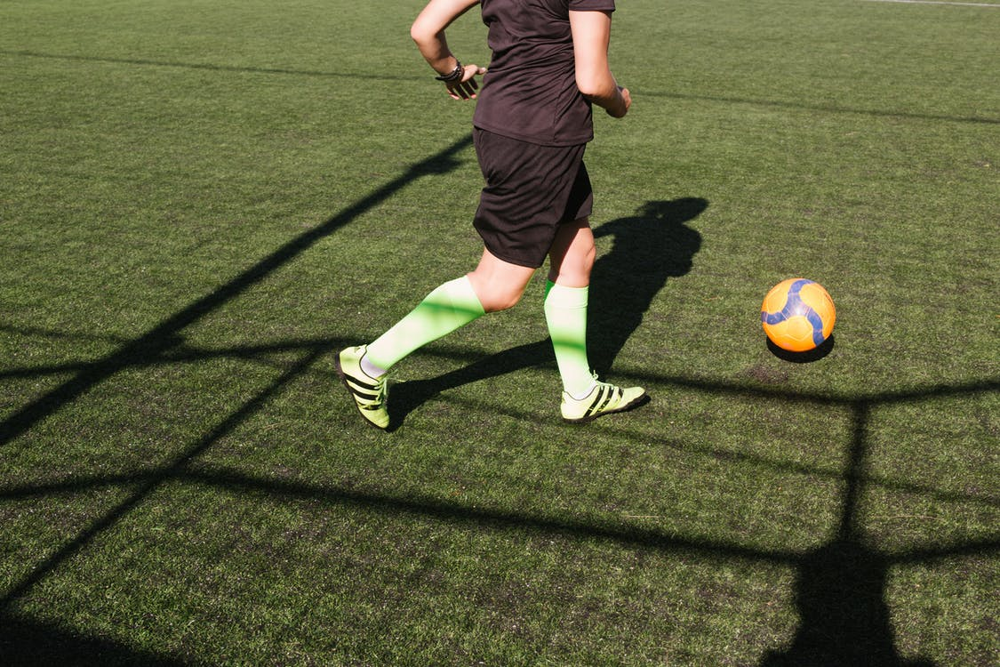 Person Wearing Black Soccer Jersey Playing Soccer