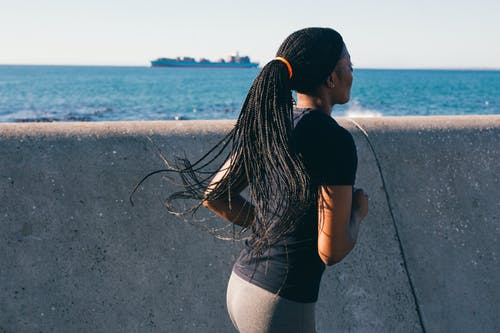 Photo of Woman Running Near Sea Wall
