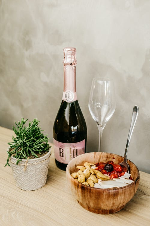 Wine Bottle Beside Wine Glass and Bowl of Food