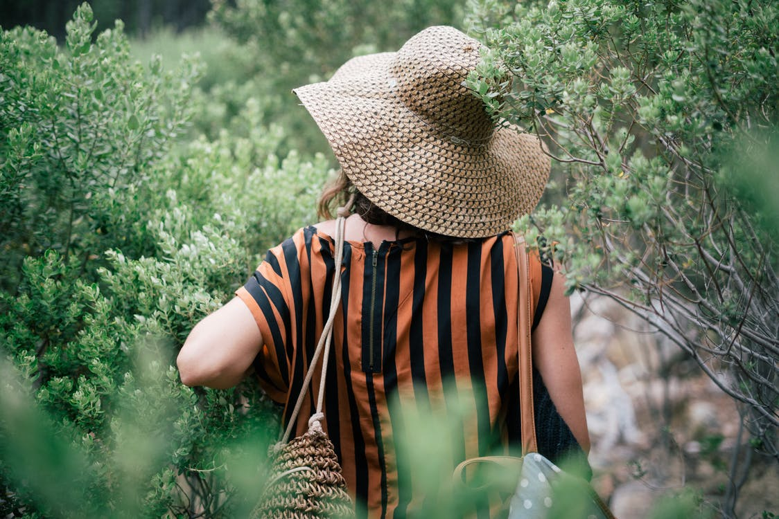 Person Wearing Straw Hat and Orange and Black Stripe Shirt